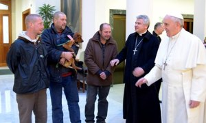 Pope Francis and archbishop Konrad Krajewski welcome some homeless men at the Vatican
